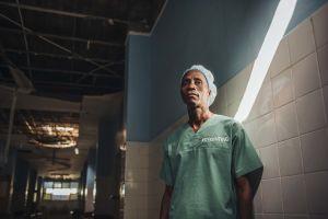 Kirurgi seisoo sairaalan käytävällä, jonka katto on osittain romahtanut.