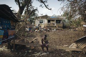 Nainen istuu puuparrun päällä, ympärillä näkyy Idai-hirmumyrskyn tuhoja.