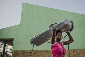 Nainen kantaa hätämajoituspakettia. Taustalla on vihreä seinä.