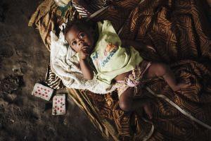 Pikkuvauva makaa savimajan lattialla. Hänen vieressä on pelikortit.
