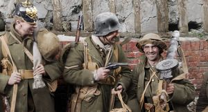 Valokuva ensimmäisen maailmansodan ajalta. Kolme miestiä seisoo rivissä tiiliseinää vasten aseiden kanssa, ja yksi miehistä osoittaa käsiaseella toista. Peter Jacksonin dokumenttielokuvasta They shall not grow old.