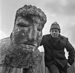 Mustavalkoisessa arkistokuvassa pipopäinen mies ja suurikokoinen veistos, josta erotettavissa kasvot