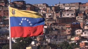 Venezuelan lippu, taustalla slummia.