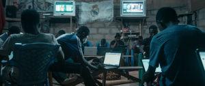 Ghanalaismiehet istuvat tietokoneiden ääressä