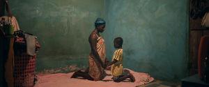 Ghanalaisnainen on lattialla polvillaan lapsen kanssa ja pitää häntä kädestä