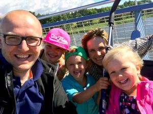 en familj med tre döttrar är ute på en båt, alla tittar mot kameran.