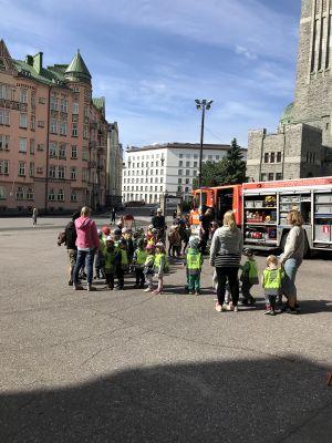 En grupp med barn och vuxna framför en brandbil.