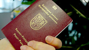 Finländskt vinrött pass med text i guldfärg.
