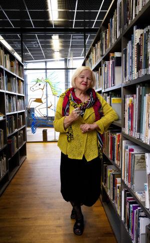 Aulikki Oksanen seisoo kirjastossa kirjojen keskellä.