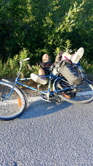 Juha makaa pyöränsä kanssa ojassa jalka ylhäällä.
