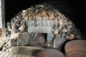 Isoista kivistä koottu kiuas hämärän Hattulan saunassa.