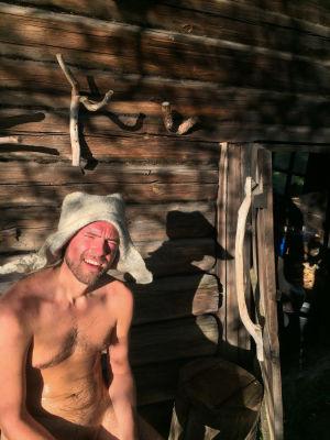 Juha istuu punakkana saunan ulkopuolella vilvottelemassa itsehuovutettu huopahattu päässään.