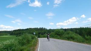 Matti pyöräilee kesäisessä maisemassa ilman käsiä.
