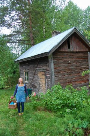 Selma Kilpi seisoo hymyillen vanhan saunan edessä kädessään kori.