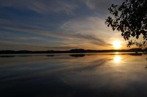 Aurinko laskee keltaisenaan suomalaiseen järvimaisemaan.