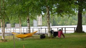Keltainen riippumatto riippuu puiden välissä.