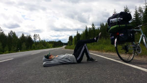 Matti makaa moottoritiellä kädet päänsä alla ja toinen jalka ylhäällä pakattu pyörä vierellään.