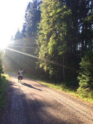 Soratiellä pyöräilevä vilkuttaa taakseen, aurinko siivilöityy puiden lävitse ja tuo kuvaan kauniin valon.