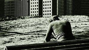 Mies istuu tuhoutuneessa kaupungissa penkillä