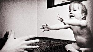 Pieni lapsi kurottaa syliin itkuisena.