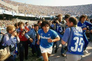 Diego Maradona juoksee S.C.C. Napolin kentälle ensimmäistä kertaa vuonna 1984 kuvaajien ympäröimänä.