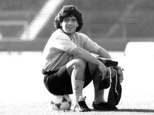 Jalkapalloilija Diego Maradona istuu pallon päällä vuonna 1989.