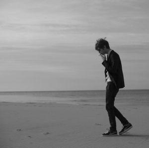 mustavalkokuvassa Miki Liukkonen kävelee rannalla ja polttaa savuketta.