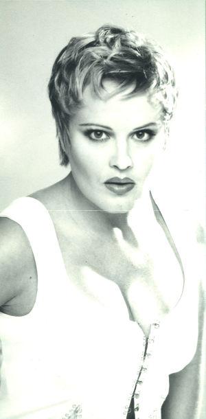 Kikka pressikuvassa 1990-luvun puolivälissä. Mustavalkoinen kuva, jossa Kikalla päällä valkoinen korsetti, jossa hakaset etupuolella.