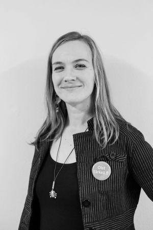 En svartvit bild på Minna Saunders. Hon har en långrandig jacka med en knapp på. Knappen har texten Olet tärkeä.fi.