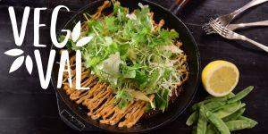 En japansk omelett i en gjutjärnspanna. På omeletten finns det mycket grön sallad. Vid sidan om pannan ligger några gafflar, en citron och oskalade ärtor.