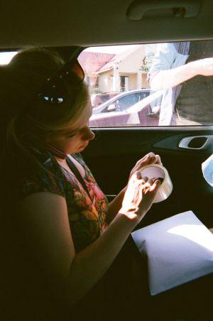 Kertakäyttökameralla otettu kuva Maustetyttöjen Kaisa Karjalaisesta autossa.
