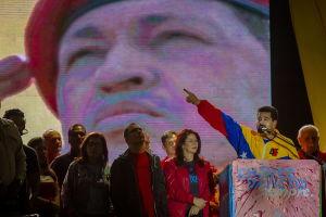 Nicolas Maduro verkkatakissa puhujan pöntössä, taustalle projisoitu Hugo Chavezin kuva