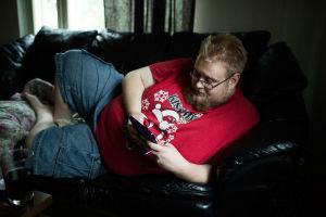 Saku Heinonen ligger på soffan och spelar.
