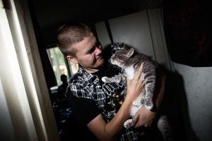 Ung man håller en grå katt i famnen.