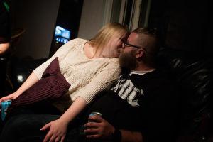 Ett ungt par sitter i en stol och kysser varandra.