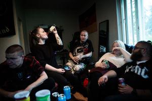 Unga sitter i ett rum och dricker alkohol.