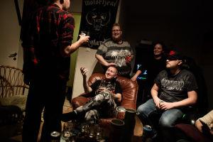 Ynglingar står runt Sami Heinonen i ett mörkt rum.