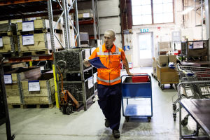 Sami Heinonen iklädd orange väst drar en kärra i fabrikshall.