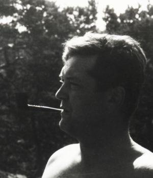 svartvitt foto taget utomhus av en man i profil med en lång cigarett i munnen