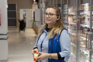 En kvinna i s-gruppens blå dräkt står i en butik och håller i en rulle med orange rea-lappar.