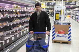 En man i mörka kläder och långt skägg skuffar på en varukärra inne i en matbutik.