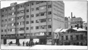 Sotilaita pommitetun Pohjoismaiden Yhdyspankin talon edessä. Kuvassa näkyvät elokuvateatteri Palatsin sekä ravintolan ja kahvilan nimikyltit.