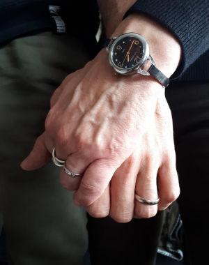 Två ringprydda fingrar sammanflätade.