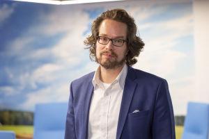 En man i vit skjorta och blå kostym står framför en vägg som ser ut som en blå himmel. Han tittar in i kameran.