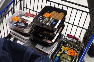 Rödmärkta köttprodukter i en shoppingkärra.