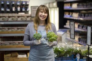 En kvinna står i en mataffär och håller i broccoli.