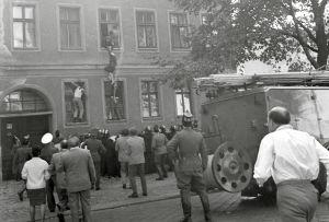 En svartvit bild från 1960-talet. Människor har samlats ute på gatan framför en byggnad och tittar på tre människor som försöker klättra in och ut genom fönster på väggen.