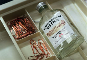 En flaska med Koskenkorvan viinaa ligger i en skrivbordslåda tillsammans med en massa gem.