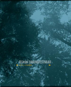 Taivasta näkyy puiden latvojen läpi. Teeman elokuvafestivaali 2019 -taustakuva.