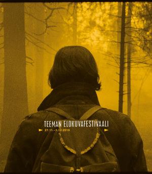 Reppuselkäinen hahmo takaapäin nähtynä sumuisessa metsässä. Teeman elokuvafestivaali 2019 -taustakuva.